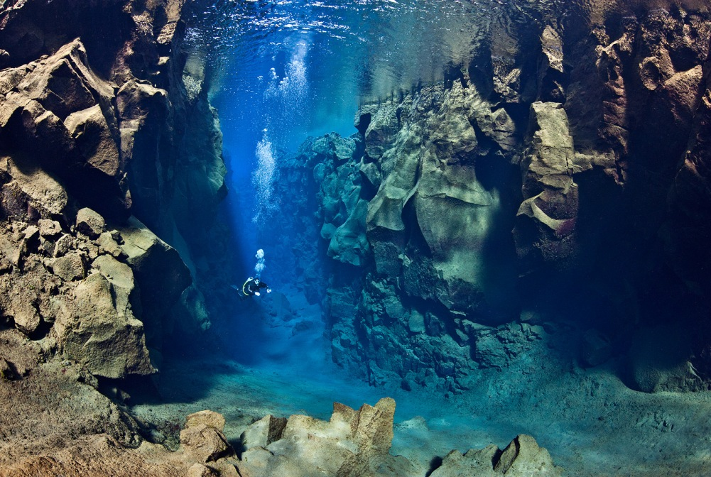 A diver explores the cathedral at Silfra canyon, a deep fault filled with fresh water in the rift valley between the Eurasian and American tectonic plates) at Thingvellir National Park, Iceland. In this photo the American plate is on the left and the Eurasian plate on the right.